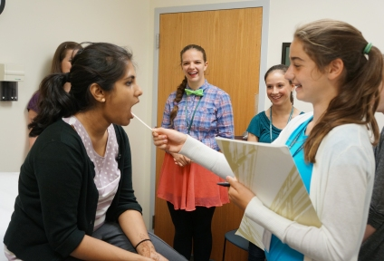 Girls Science Discovery Day participants try their hand at being a physician.