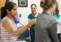 Participants in Girls Science Discovery Day learn basic physical exam skills.